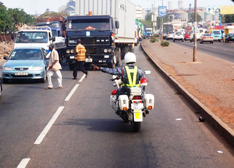 """Making a way where there is no way: our miracle-working police escort named """"Hope""""  clears a path for our tour bus down the wrong side of a busy street"""
