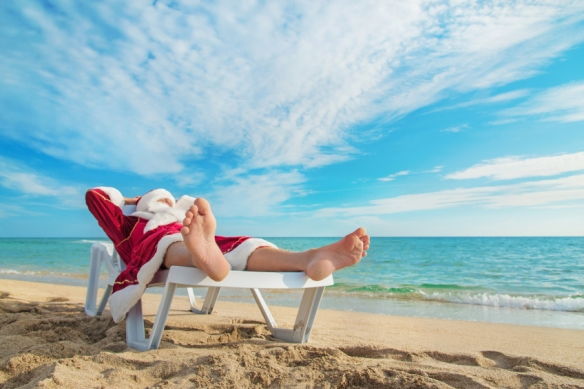 sunbathing Santa Claus relaxing in bedstone on tropical sandy be